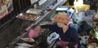 Lady Serving Fish on Boat at Taling Chan Floating Market Bangkok Thailand